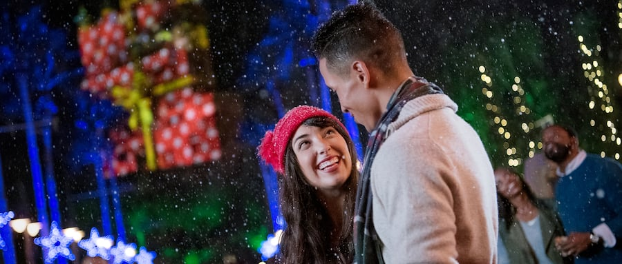 A happy couple stands on Sunset Boulevard as snow falls around them