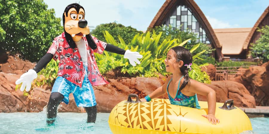 A young girl holding a pool float while hanging out with Goofy in a pool at Aulani Resort