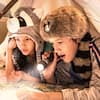 Two kids wearing Frontierland inspired novelty hats read a map with a flashlight and a small lantern underneath a makeshift teepee on their Resort bed
