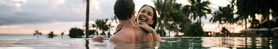 Two smiling adults in an infinity pool, with palms silhouetted along the shoreline