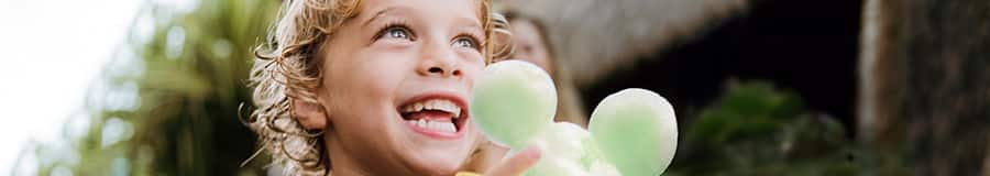 Smiling young girl holding a light green shave ice