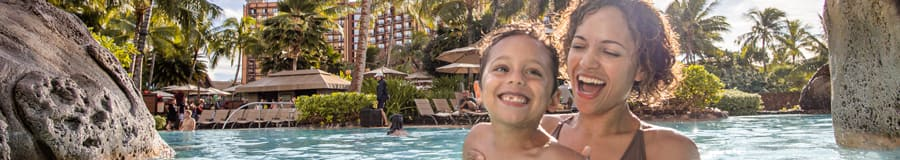 A laughing mother holds a smiling child in a large pool at Aulani Resort, with lounge chairs, palm trees and buildings of the Resort in the background