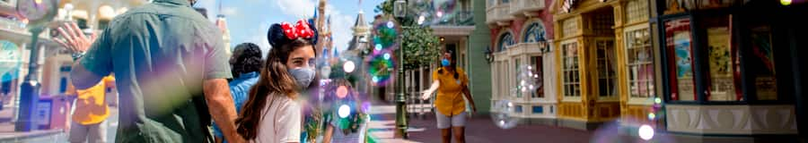 A family walking down Main Street USA at Magic Kingdom park, while Cast Members wave at them