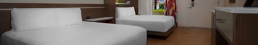 Duas camas grandes com uma prateleira entre elas, perto de uma janela com cortinas suspensas longas