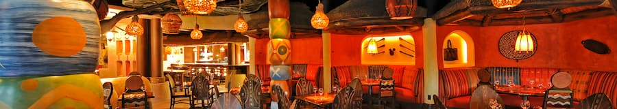 Faroles colgantes sobre mesas con sillas y decoraciones en la pared de diseño tribal