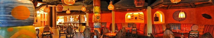 Lanternas suspensas sobre mesas com cadeiras com design tribal e decoração de parede