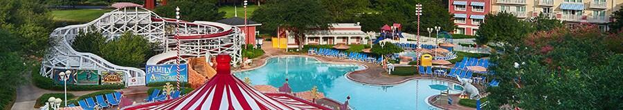 La piscine du Disney's BoardWalk Inn avec 2bâtiments à plusieurs étages, des arbres feuillus, un casse-croûte en forme de carrousel et une glissade d'eau façonnée pour ressembler à des montagnes russes