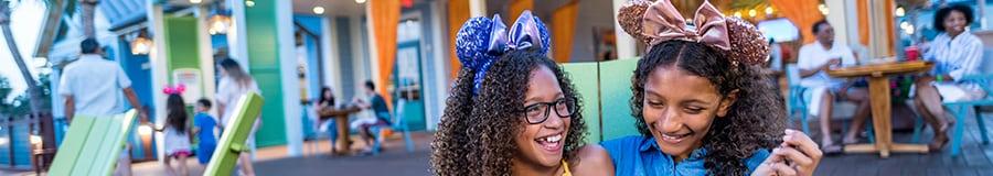 2niñas sonrientes con diademas de diseñador de Minnie Mouse están sentadas juntas