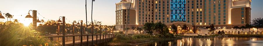 Un pont s'étend au-dessus d'un grand plan d'eau menant au bâtiment d'un hôtel