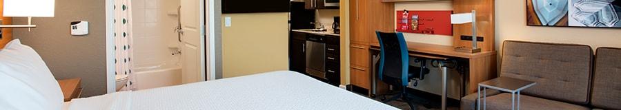 Uma cama king em uma suíte de hotel bem mobiliada, com um banheiro e uma cozinha ao fundo
