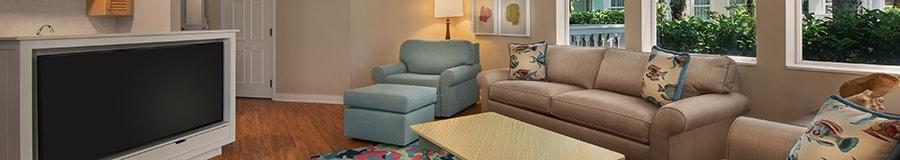 Deux canapés et un fauteuil avec un pouf placés devant un grand téléviseur à écran plat dans un salon