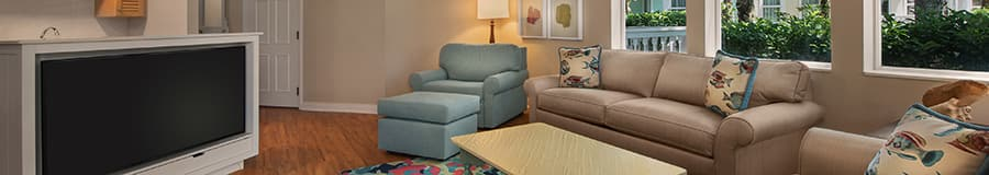 Two couches and a chair with an ottoman pointed at a large flat screen television in a living room