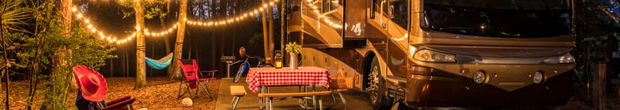An R V parked in a forest campsite with popcorn lights, a picnic table, camp chairs, a hammock, lanterns and a golf cart.