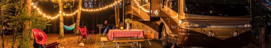 Un RV estacionado en un campamento en el bosque con una cadena de luces, una mesa de pícnic, sillas de camping, una hamaca, linternas y un carrito de golf.