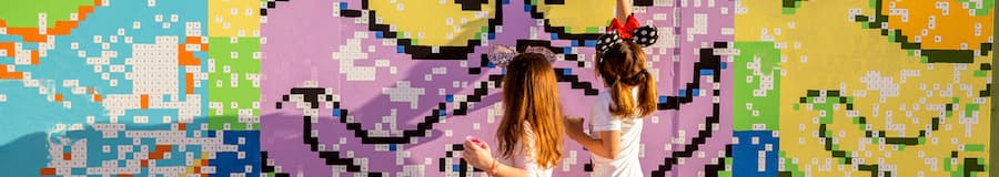 Two young girls interact with an art wall