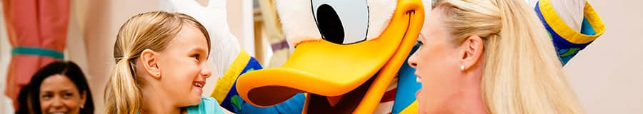 Donald Duck greets a mother and her young daughter at their table