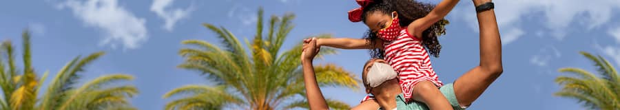 A little girl sits on her father's shoulders in an outdoor setting with palm trees