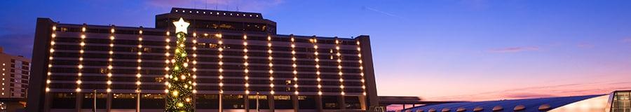 Un árbol de Navidad encendido frente al Disney's Contemporary Resort iluminado por la noche