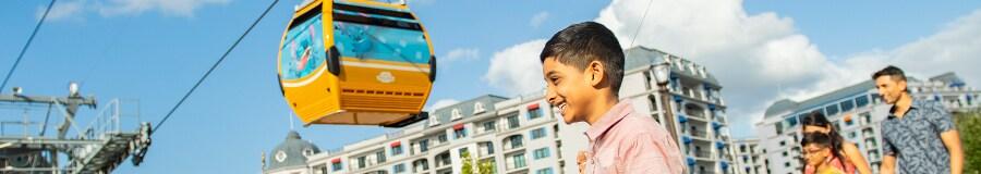 A father and son stroll beneath a Disney Skyliner gondola