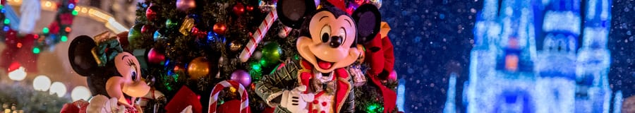 Minnie and Mickey wave to Guests while on a Christmas themed parade float
