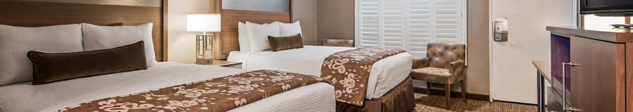 A hotel guest room features 2 queen size beds, a nightstand, and lamp