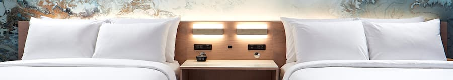 Dos camas Queen Size estándar con una mesa de noche con reloj y luces montadas en la pared entre ellas