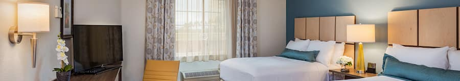 A studio suite features 2 queen sized beds with pillows and wood headboards, an all in one desk, table and dresser area, 2 chairs, floral arrangements, a nightstand, television and wall sconce