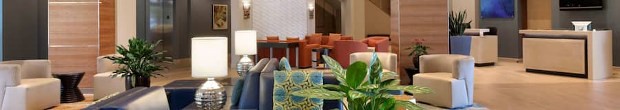 The lobby of a hotel with sofas, chairs and tables decorated with plants