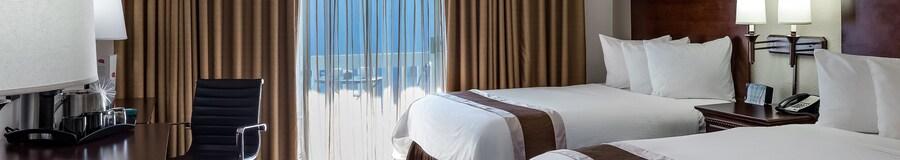 Una habitación de hotel con 2 camas matrimoniales, silla, cómoda y escritorio