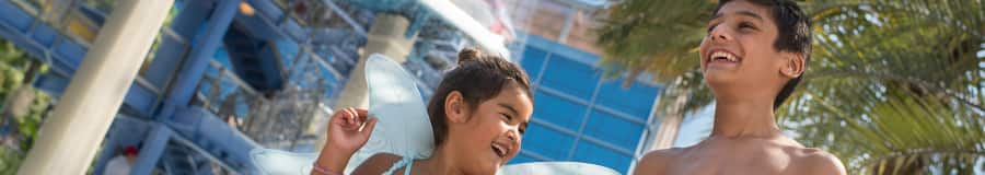 A brother and sister playing near a waterslide at Disneyland Hotel