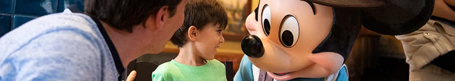 Mickey greets a young boy and his Dad at their breakfast table
