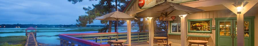 Picnic tables, umbrellas and benches sit outside the Broad Creek Mercantile shop overlooking the water