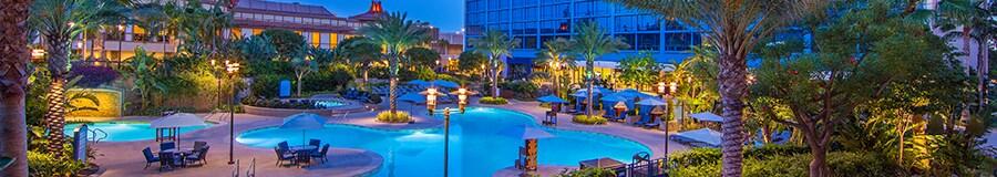 Al anochecer, la piscina y el área de jacuzzis brillan con luz ambiental debajo de las palmeras