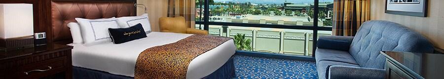 Una cómoda, un sofá, una cama King Size con cabecera, un sillón, además de una ventana panorámica