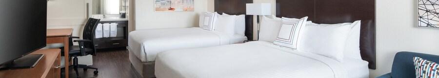 Un sofá y dos camas Queen Size con cabeceras situadas frente a una cómoda con televisor y un escritorio con silla, además de un tocador