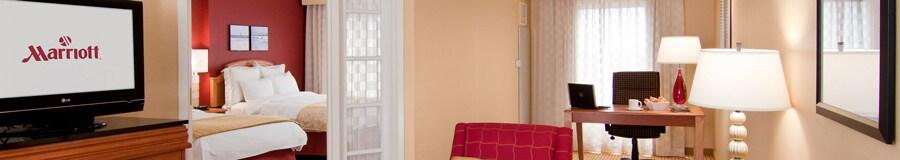 Sala de estar que cuenta con cómoda con televisor, un sillón y escritorio junto a una habitación con dos camas matrimoniales