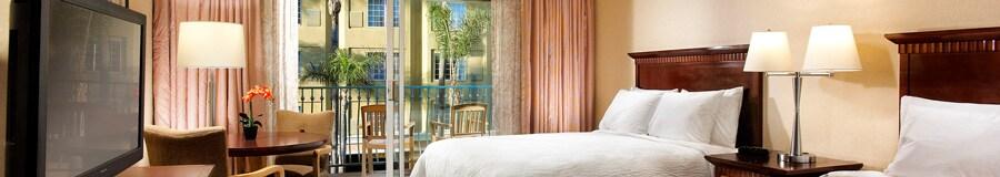 Dos camas Queen Size frente a una cómoda con un televisor y una mesa redonda con dos sillas, además de un balcón