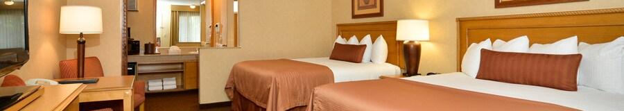 Dos camas matrimoniales frente a una cómoda con un televisor, una mesa con dos sillas, además de un tocador