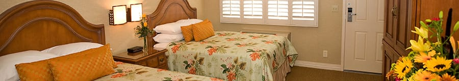 Two queen beds with wooden headboards across from an armoire and, beyond, windows with shutters