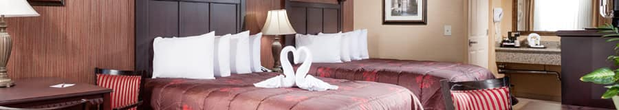 Kissing towel swans sit on one of the 2 luxurious beds amidst contemporary décor