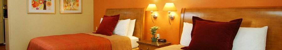 Dos camas Queen Size con cabeceras de madera separadas por una mesa de noche y doslámparas fijadas a la pared