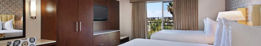 2 queen beds, curtained balcony, contemporary built in wooden armoire and drawers, wall mounted TV