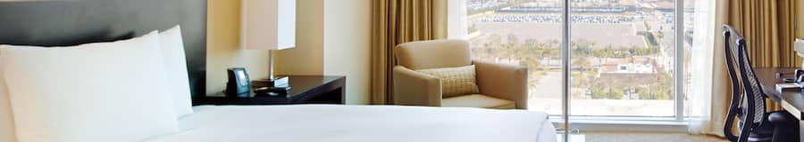 The Hilton Anaheim king room features a contemporary king size bed, arm chair, desk, dresser and TV