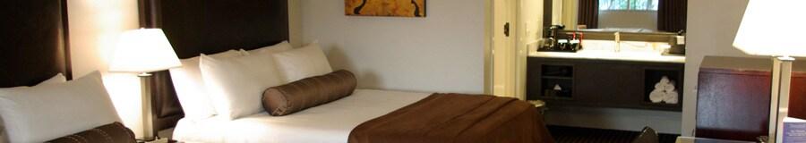 Dos camas con cabeceras y, más allá, un área de tocador