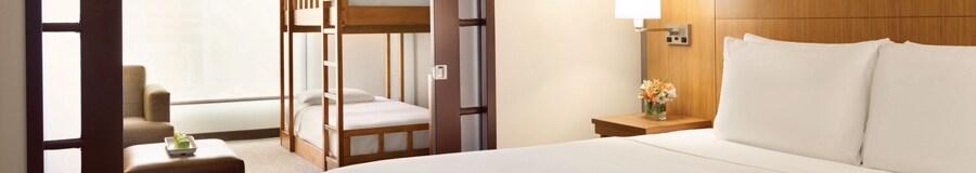 Una suite estilo familiar iluminada en Hyatt Place at Anaheim Resort/Convention Center con dos dormitorios equipados con una cama King Size y literas individuales