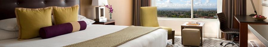 Una cama King Size con cabecera, mesa de noche, sillón, escritorio y, al fondo, una ventana