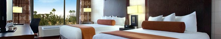 Dos camas Queen Size con cabeceras frente a una cómoda con TV y un escritorio, además de una ventana
