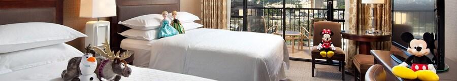 Una cama Queen Size frente a una cómoda con TV, además de una mesa redonda, dos sillones y un balcón