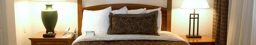 Una cama matrimonial con cabecera de madera entre mesas de noche con lámparas