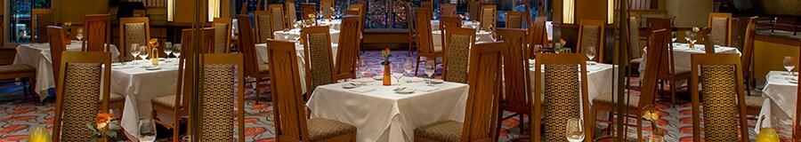 Mesas para cuatro con sillas de respaldo alto listas para que los Huéspedes cenen en un comedor elegante